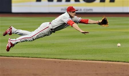 Philadelphia Phillies second baseman Chase Utley dives for a single by New York Mets batter Angel Pagan in New York